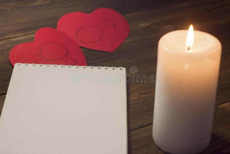 Κερί φραγμών κεριών και δύο καρδιών σε ένα ξύλινο σημειωματάριο υποβάθρου στοκ φωτογραφίες με δικαίωμα ελεύθερης χρήσης