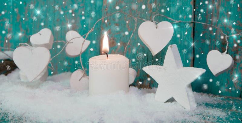 Κερί Χριστουγέννων στο λευκό με τις τυρκουάζ καρδιές, το ξύλο και το χιόνι φ στοκ φωτογραφία