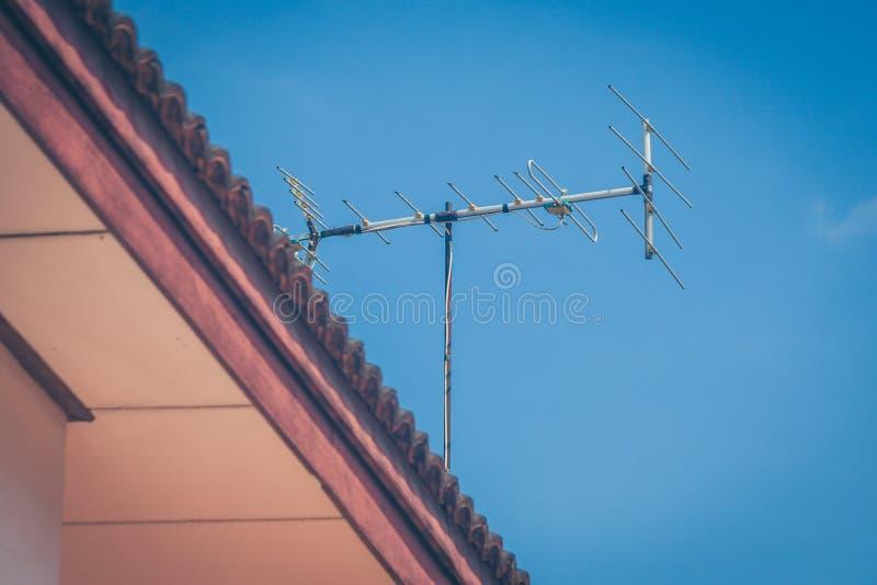 Κεραία TV στη στέγη του σπιτιού με το υπόβαθρο μπλε ουρανού στοκ εικόνα με δικαίωμα ελεύθερης χρήσης