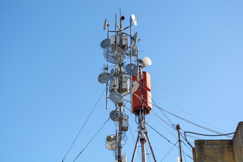 Κεραίες μερών του ασύρματου δικτύου, των τηλεπικοινωνιών και των δορυφορικών πιάτων σε μια στέγη οικοδόμησης στοκ εικόνα