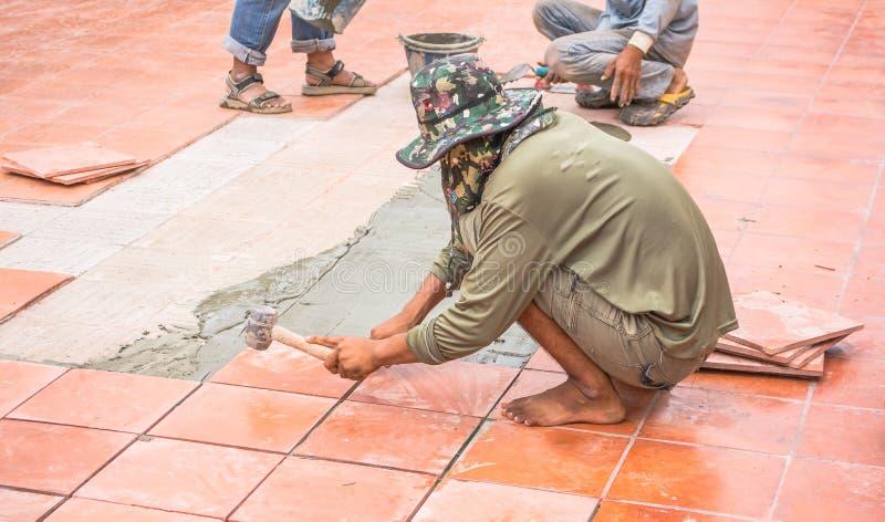 Κεραμίδι και εγκατάσταση πατωμάτων επισκευής εργαζομένων για την οικοδόμηση στοκ φωτογραφίες