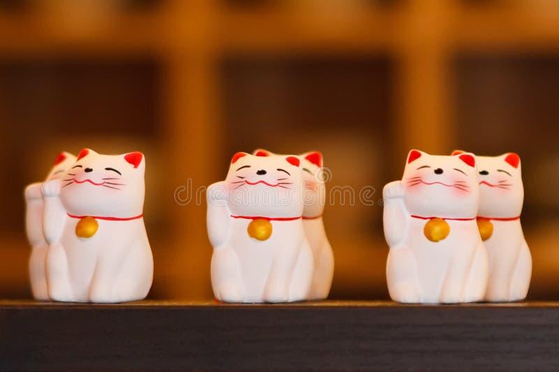 Κεραμικές κούκλες γατών Maneki Neko στο ξύλινο ράφι στοκ εικόνες