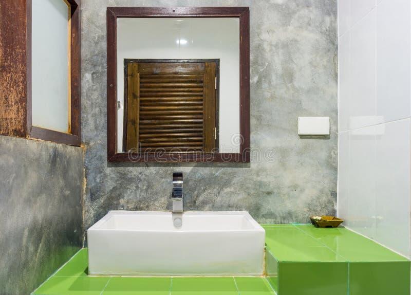 Κεραμικοί washbasin, το κύπελλο και ο καθρέφτης στα πράσινα κεραμικά κεραμίδια αντιμετωπίζουν στοκ εικόνες