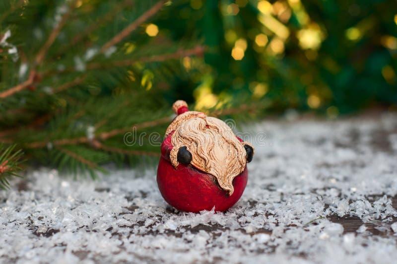 Κεραμικός Άγιος Βασίλης σε μια μικρή χιονισμένη ξύλινη επιφάνεια στοκ φωτογραφία