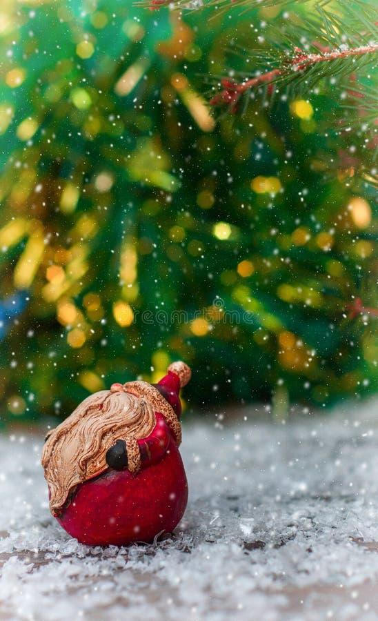 Κεραμικός Άγιος Βασίλης σε μια μικρή χιονισμένη ξύλινη επιφάνεια στοκ εικόνες