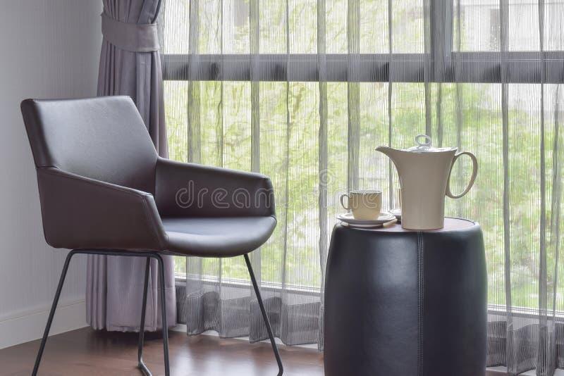 Κεραμικός καφές που τίθεται στον πίνακα με τη μαύρη εύκολη καρέκλα δέρματος μέσα στοκ φωτογραφία
