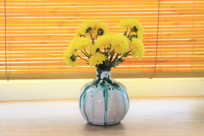 Κεραμικό βάζο με τα κίτρινα λουλούδια στοκ εικόνα
