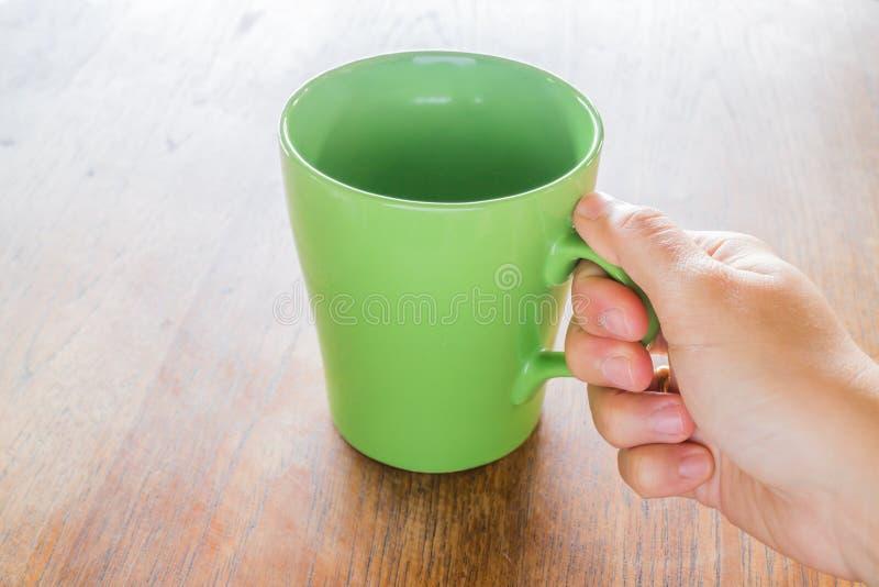 Κεραμικό φλυτζάνι καφέ λαβής χεριών στοκ εικόνες