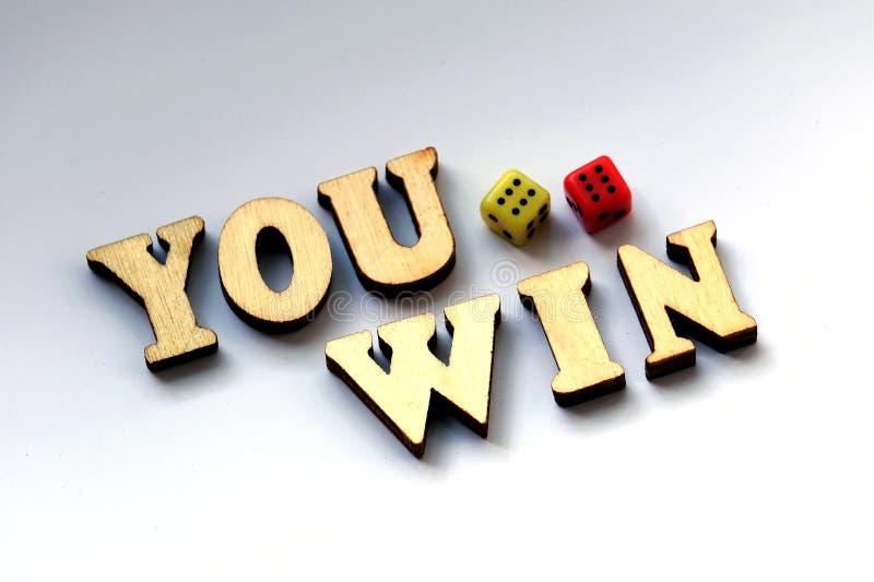 Κερδίζετε Οι ξύλινες επιστολές και χωρίζουν σε τετράγωνα σε ένα άσπρο υπόβαθρο στοκ εικόνα