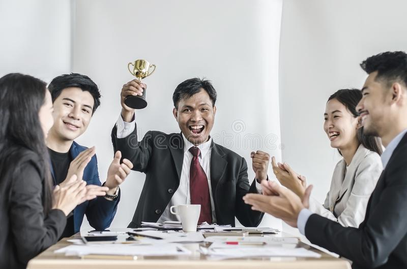 Κερδίζοντας επιχειρησιακή ομάδα με έναν ανώτερο υπάλληλο ατόμων που κρατά ένα χρυσό τρόπαιο στοκ φωτογραφία