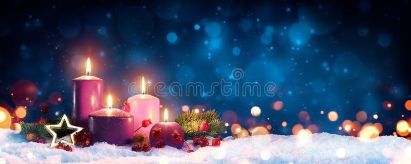 Κεριά εμφάνισης στο στεφάνι Χριστουγέννων στοκ φωτογραφία