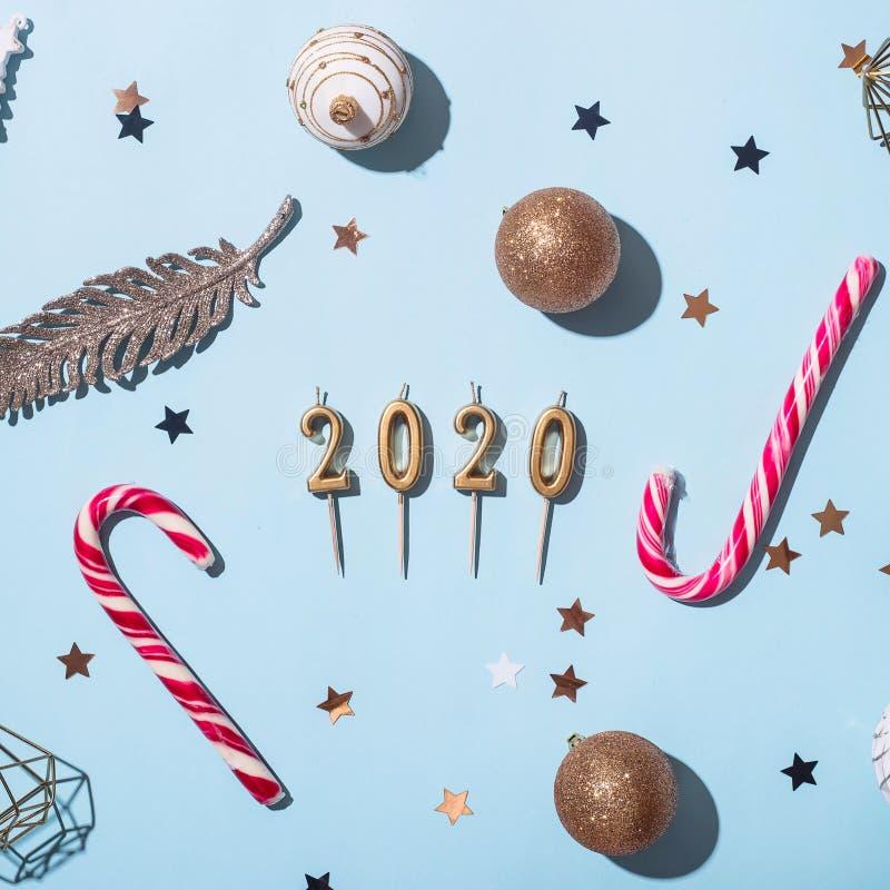 Κεριά με μορφή των σχημάτων 2020 μεταξύ των διακοσμήσεων Χριστουγέννων σε ένα μπλε υπόβαθρο στοκ εικόνες με δικαίωμα ελεύθερης χρήσης