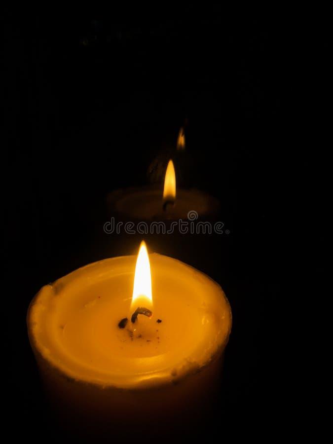 Κεριά που καίνε τη νύχτα Άσπρα κεριά που καίνε στο σκοτάδι με στοκ εικόνες