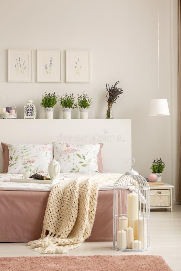Κεριά στο κλουβί πουλιών που τοποθετείται στο πάτωμα από το διπλό κρεβάτι με το brea στοκ εικόνα