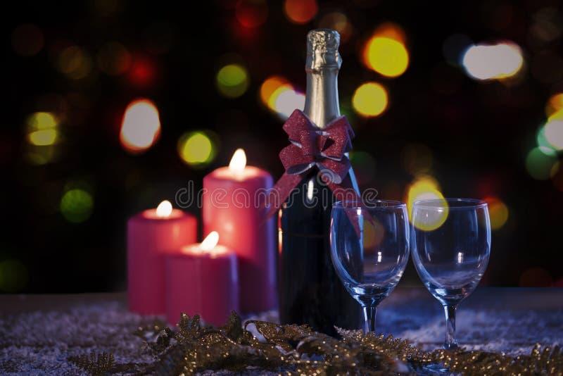 Κεριά Χριστουγέννων με το μπουκάλι σαμπάνιας πέρα από το χιόνι στοκ εικόνα
