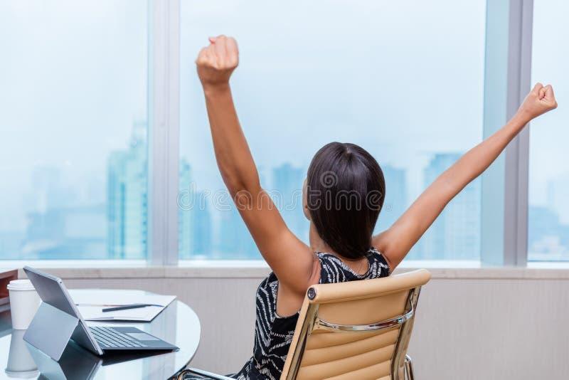 Κερδίζοντας όπλα εργαζόμενων γυναικών γραφείων επάνω στην επιτυχία στοκ φωτογραφία
