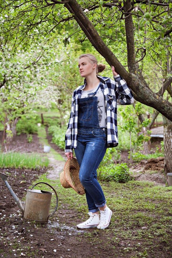 Κηπουρός γυναικών που στηρίζεται και που σκέφτεται στοκ φωτογραφία με δικαίωμα ελεύθερης χρήσης