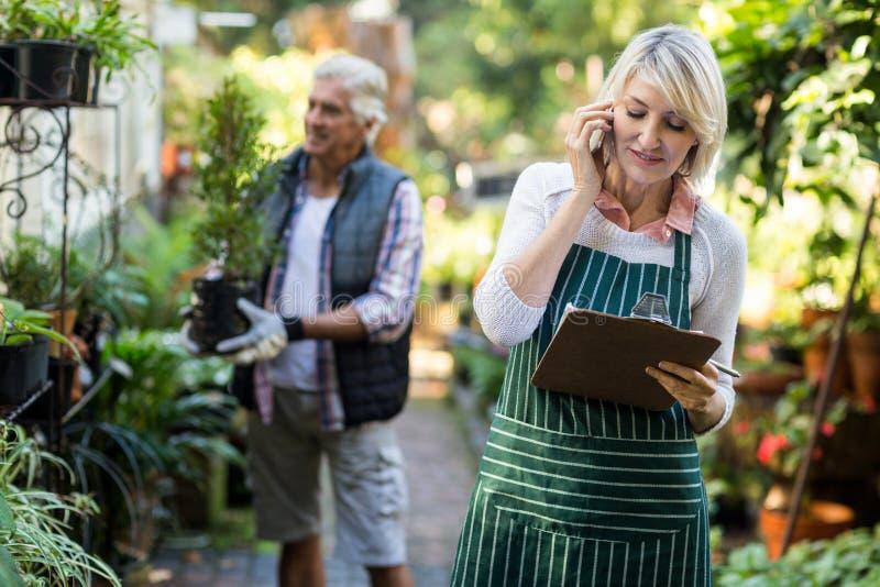 Κηπουρός που μιλά στο κινητό τηλέφωνο ενώ άτομο στο υπόβαθρο στοκ φωτογραφία