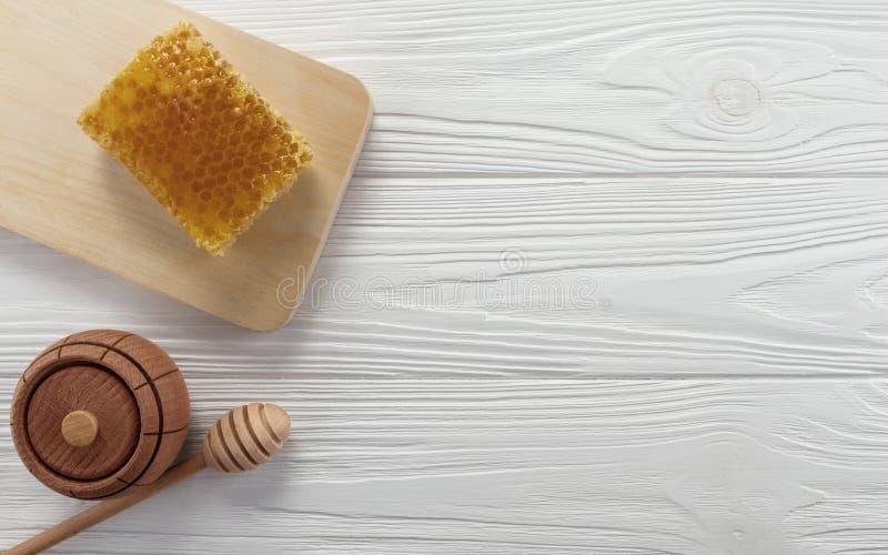 Κηρήθρα και ξύλινο βάζο μελιού στον πίνακα στοκ εικόνες με δικαίωμα ελεύθερης χρήσης