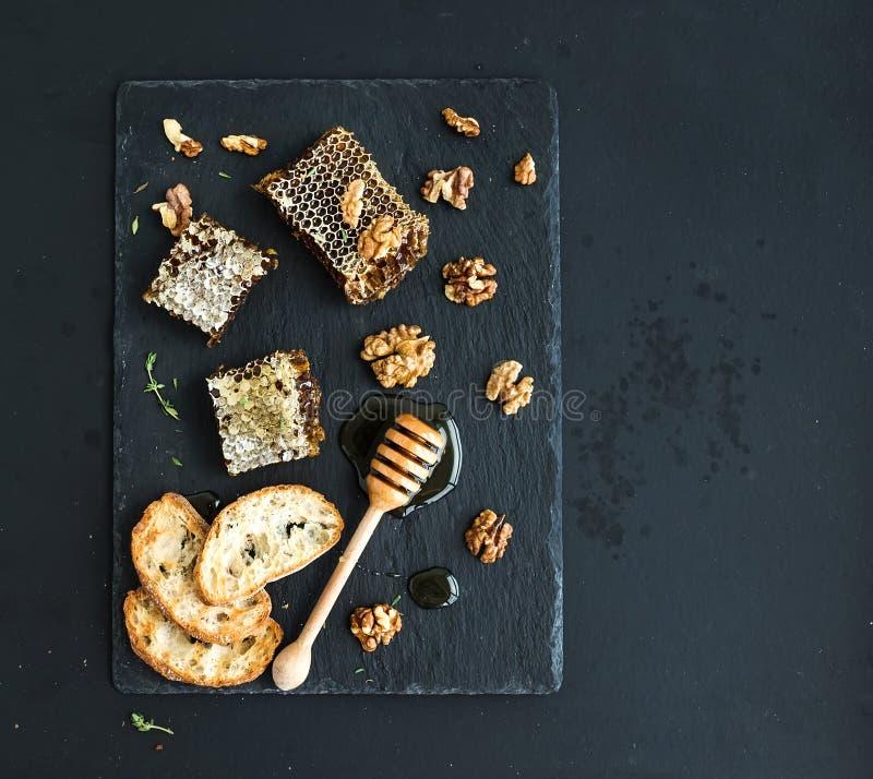 Κηρήθρα, ξύλα καρυδιάς, φέτες ψωμιού και dipper μελιού στοκ φωτογραφία