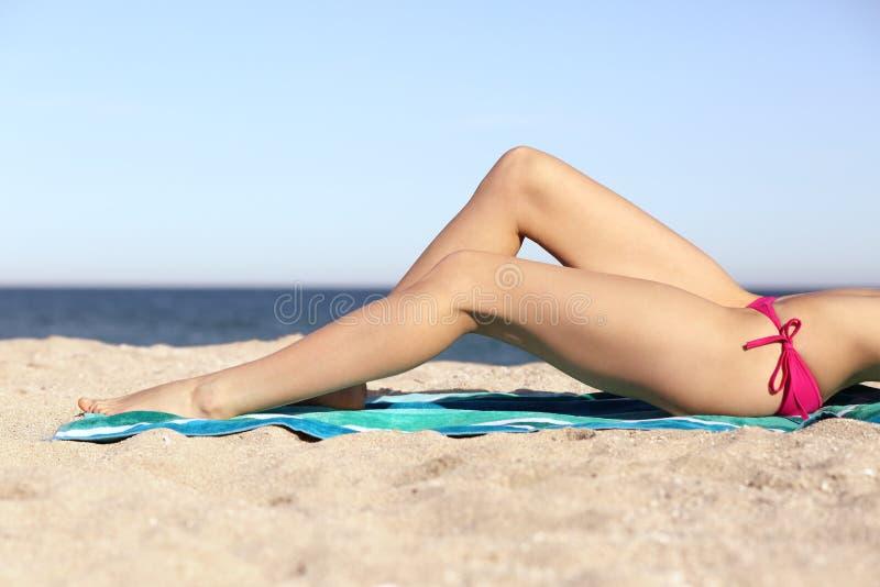 Κηρώνοντας πόδια γυναικών ομορφιάς τέλεια που κάνουν ηλιοθεραπεία στην παραλία στοκ φωτογραφίες
