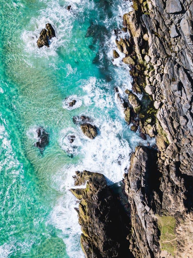 Κηφήνας παραλιών που πυροβολείται με τα κύματα και τους απότομους βράχους aqua στοκ φωτογραφίες