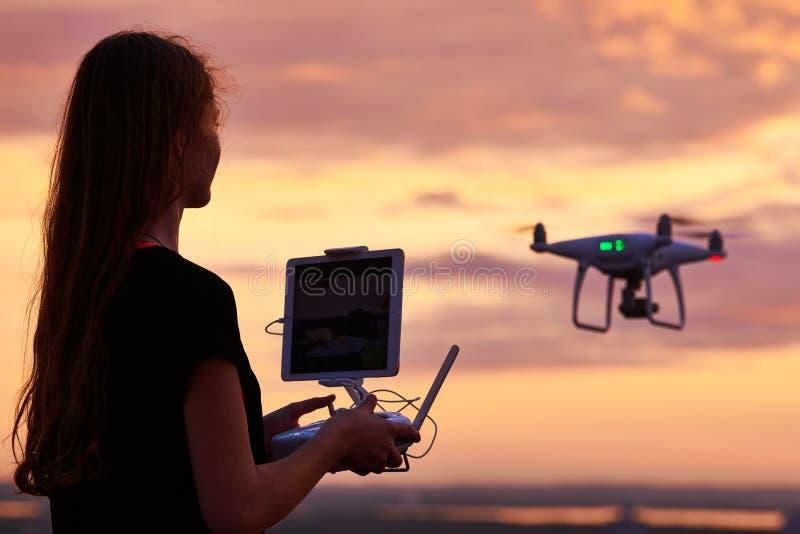 Κηφήνας quadcopter τη ψηφιακή κάμερα που χρησιμοποιείται με από τη γυναίκα στο ηλιοβασίλεμα στοκ φωτογραφία με δικαίωμα ελεύθερης χρήσης