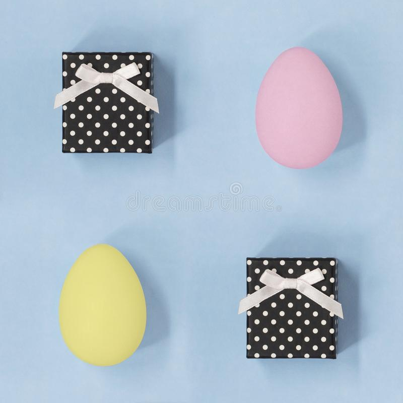 Κιβώτια δώρων και ρόδινα και κίτρινα αυγά Πάσχας σε έναν χλωμό - μπλε υπόβαθρο στοκ εικόνες με δικαίωμα ελεύθερης χρήσης
