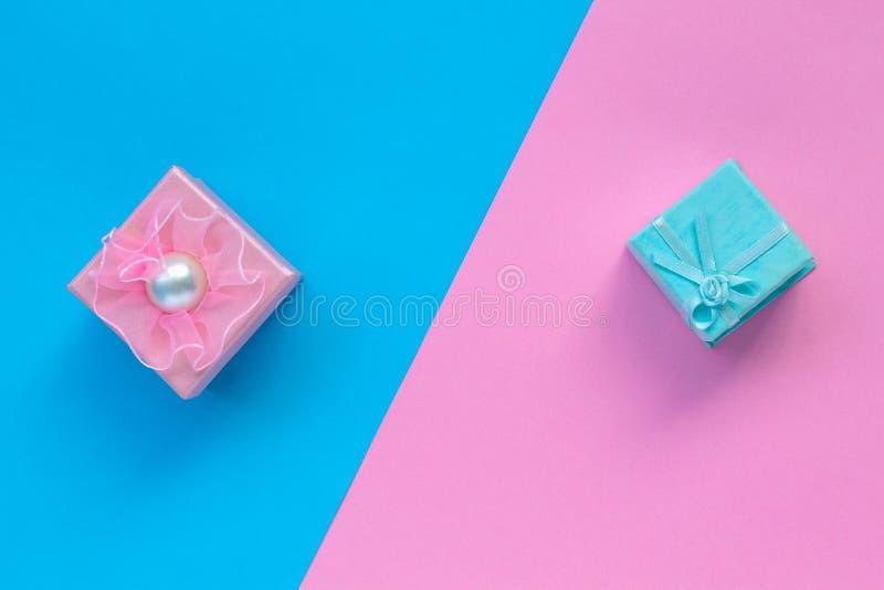 Κιβώτια δώρων με τις κορδέλλες και τόξα στη ρόδινη και μπλε τοπ άποψη υποβάθρου στοκ εικόνες