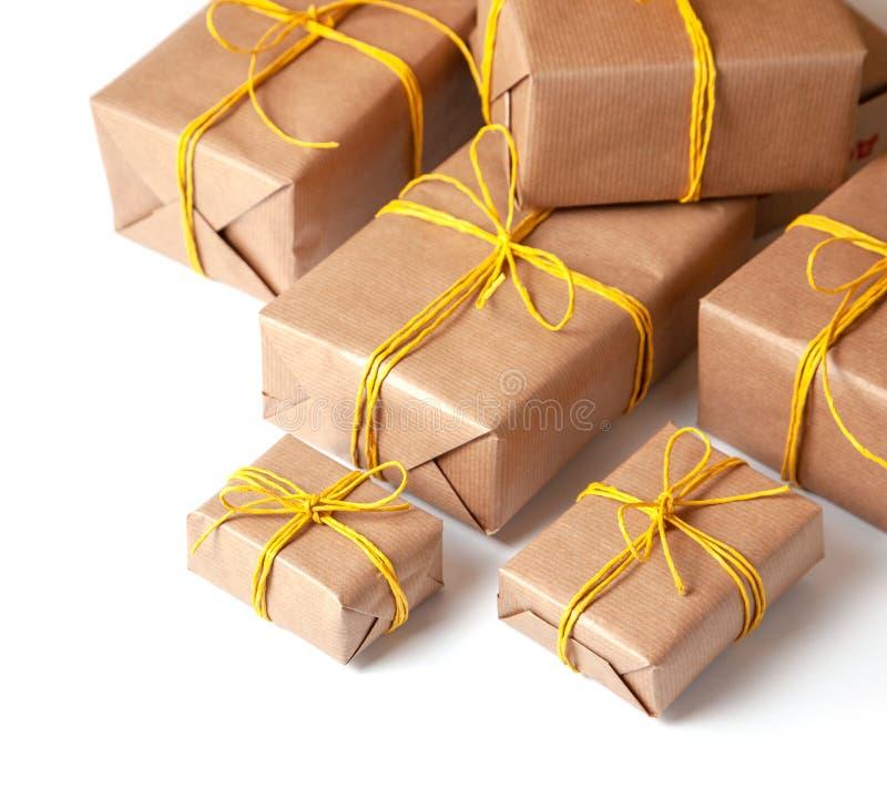 Κιβώτια δώρων στην εορταστική συσκευασία με τα χρυσά κίτρινα τόξα που απομονώνονται στο λευκό Παράδοση των δώρων από την ταχυδρομ στοκ εικόνα με δικαίωμα ελεύθερης χρήσης