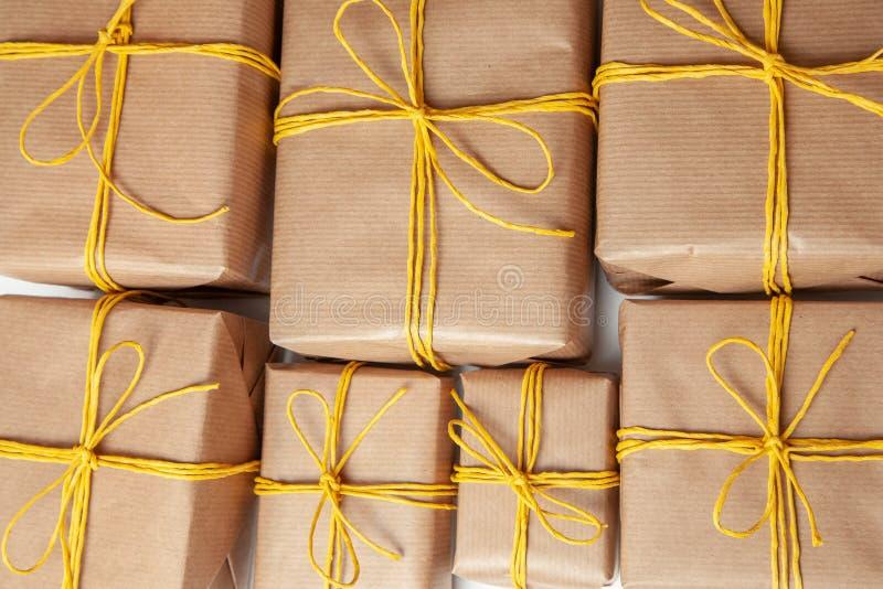 Κιβώτια δώρων στην εορταστική συσκευασία με τα χρυσά κίτρινα τόξα Παράδοση των δώρων από την ταχυδρομική υπηρεσία φορτίου στοκ φωτογραφία με δικαίωμα ελεύθερης χρήσης