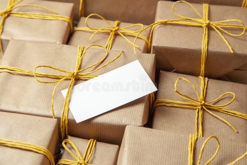 Κιβώτια δώρων σωρών στην εορταστική συσκευασία με τα χρυσή κίτρινη τόξα και τη σημείωση ή την κάρτα Παράδοση των δώρων από την τα στοκ φωτογραφίες