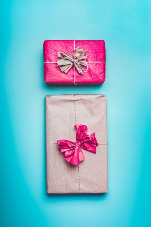 Κιβώτια δώρων χαιρετισμού στο τυλίγοντας έγγραφο με το τόξο στο μπλε υπόβαθρο, τοπ άποψη r Συγχαρητήρια, διακοπές, έννοια γενεθλί στοκ φωτογραφίες