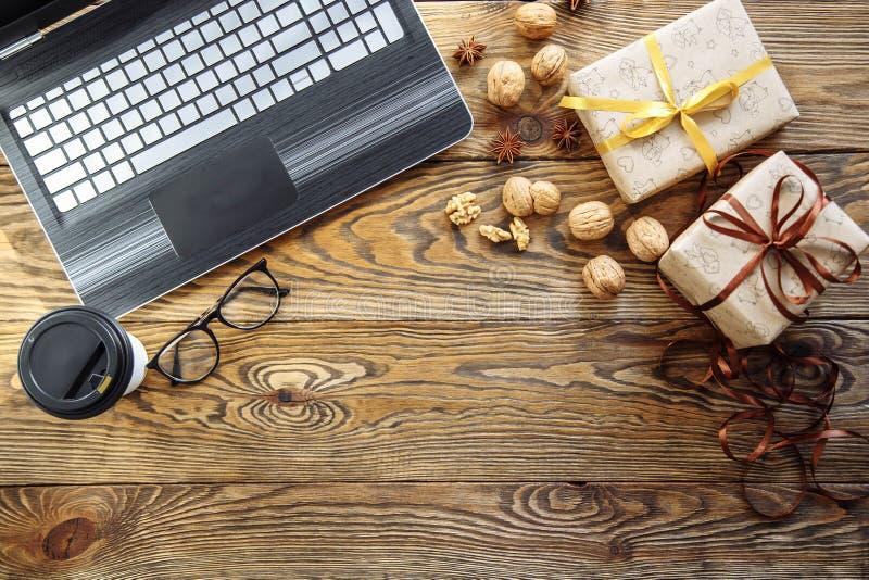Κιβώτια δώρων Χριστουγέννων, lap-top και φλυτζάνι καφέ στο ξύλινο υπόβαθρο Τοπ άποψη με το διάστημα αντιγράφων για το κείμενό σας στοκ φωτογραφία