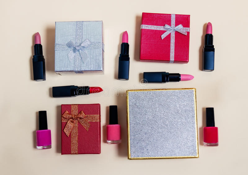 Κιβώτια δώρων και θηλυκά διακοσμητικά καλλυντικά στο μπεζ υπόβαθρο στοκ εικόνες