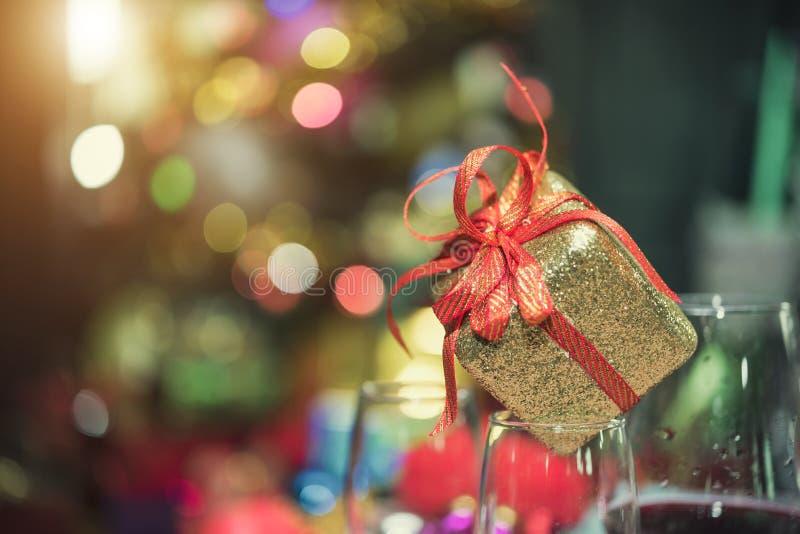 Κιβώτιο ή παρόν δώρων Χριστουγέννων με την κόκκινη κορδέλλα τόξων στο φως bokeh στοκ φωτογραφία