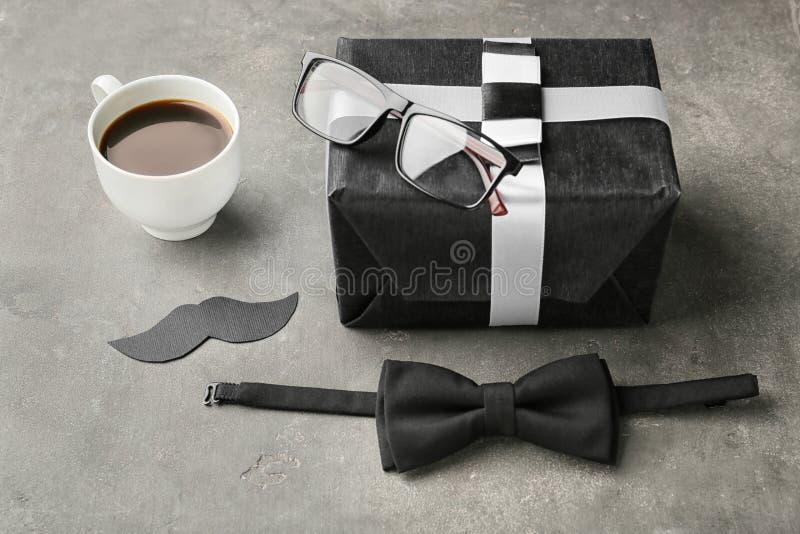 Κιβώτιο δώρων, γυαλιά, δεσμός τόξων και φλιτζάνι του καφέ στο γκρίζο υπόβαθρο Εορτασμός ημέρας πατέρα στοκ εικόνες με δικαίωμα ελεύθερης χρήσης