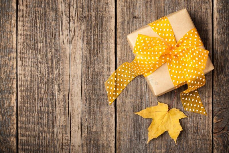 Κιβώτιο δώρων και φύλλο σφενδάμου φθινοπώρου στο ξύλινο υπόβαθρο στοκ εικόνες