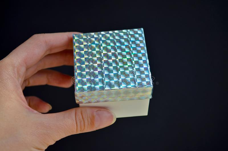 Κιβώτιο δώρων με ένα καπάκι ουράνιων τόξων στο θηλυκό χέρι στο μαύρο υπόβαθρο Ιδέα DIY πώς να διακοσμήσει ένα δώρο με μια χρωματι στοκ εικόνα με δικαίωμα ελεύθερης χρήσης