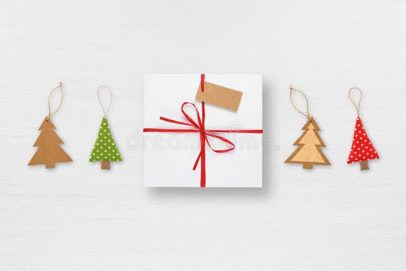 Κιβώτιο δώρων με τις διακοσμήσεις ετικεττών και χριστουγεννιάτικων δέντρων στον άσπρο πίνακα στοκ φωτογραφία με δικαίωμα ελεύθερης χρήσης