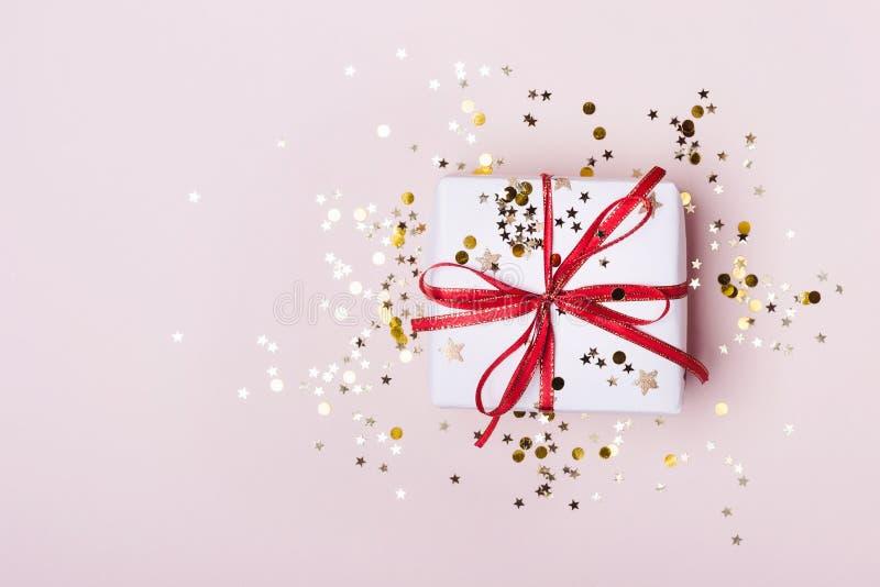 Κιβώτιο δώρων με το κόκκινο τόξο και κομφετί σπινθηρισμάτων στο ρόδινο υπόβαθρο κρητιδογραφιών r στοκ εικόνες