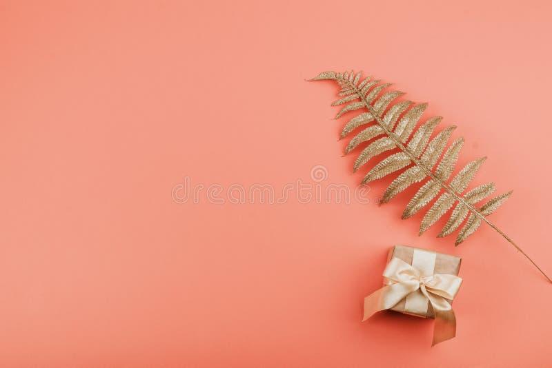 Κιβώτιο δώρων με το τόξο και χρυσά φύλλα φοινικών στο υπόβαθρο κοραλλιών Εορταστικό ελάχιστο υπόβαθρο στοκ εικόνα με δικαίωμα ελεύθερης χρήσης