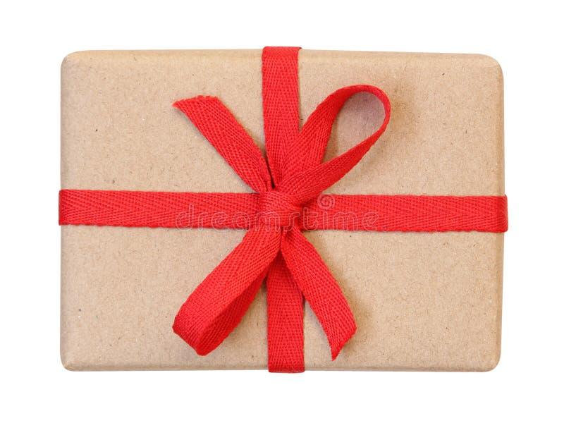 Κιβώτιο δώρων που τυλίγεται στο καφετί ανακυκλωμένο έγγραφο με την κόκκινη τοπ άποψη τόξων κορδελλών που απομονώνεται στο λευκό,  στοκ φωτογραφία