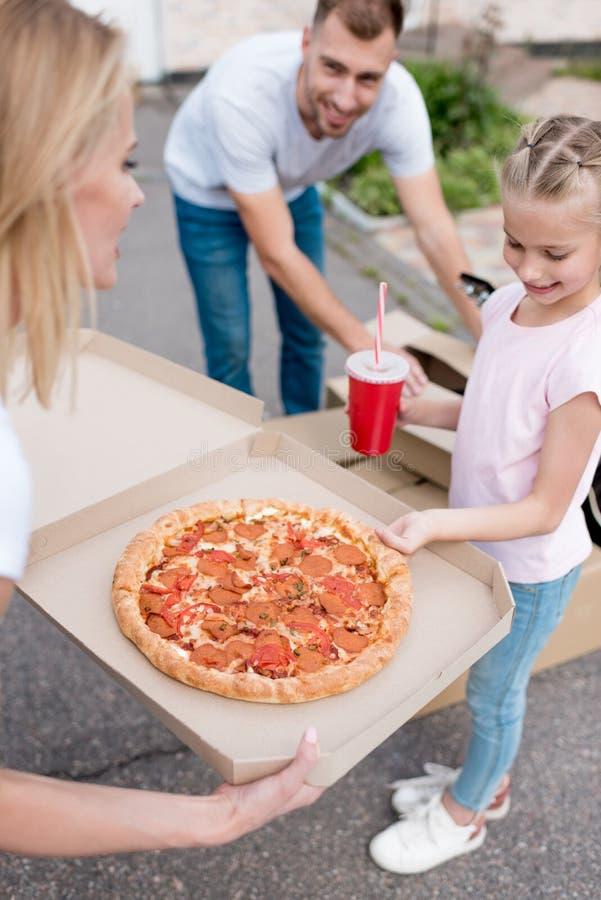 κιβώτιο εκμετάλλευσης μητέρων με την πίτσα και κόρη που παίρνει τη φέτα της πίτσας ανοίγοντας πατέρων στοκ εικόνες