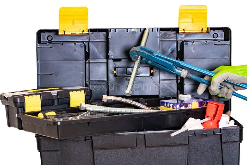 Κιβώτιο εργαλείων υδραυλικών ή ξυλουργών Μαύρο πλαστικό κιβώτιο εξαρτήσεων εργαλείων με τα ανάμεικτα εργαλεία και ένα χέρι με το  στοκ εικόνα