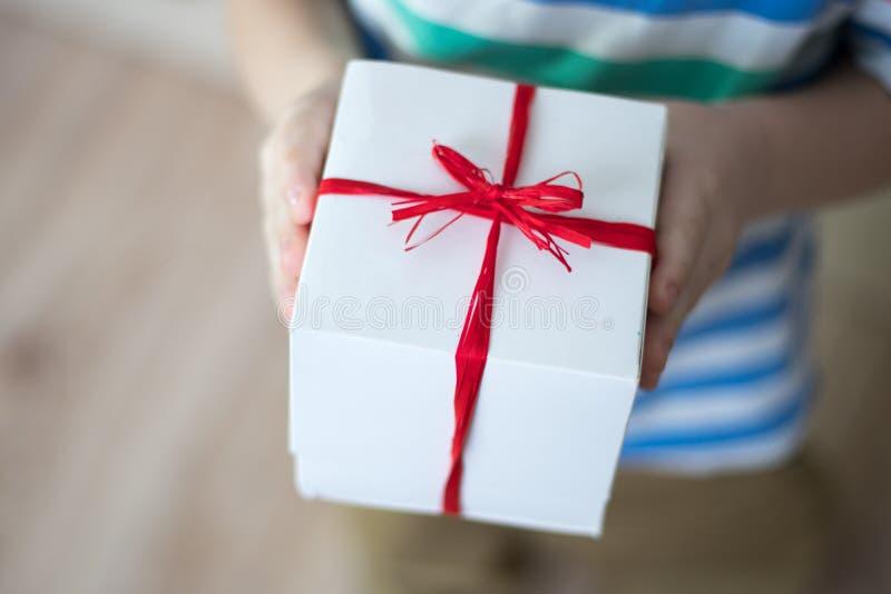 Κιβώτιο με ένα δώρο στα χέρια ενός παιδιού στοκ εικόνα με δικαίωμα ελεύθερης χρήσης