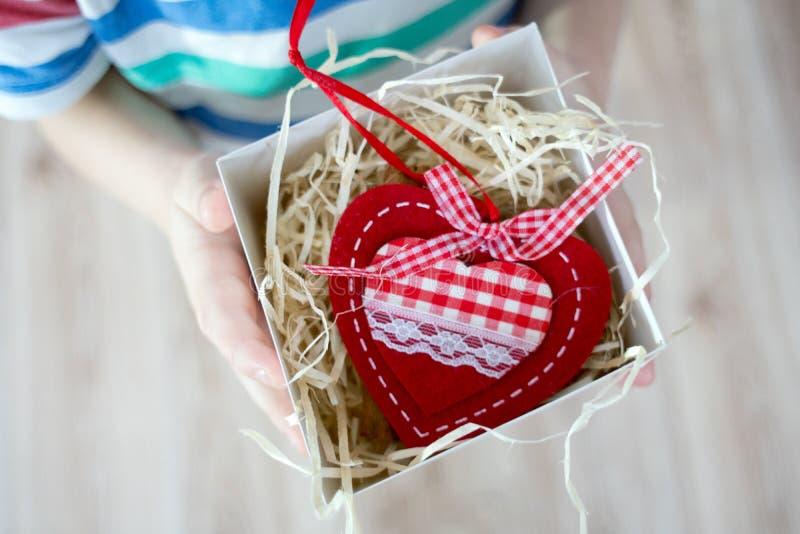 Κιβώτιο με μια καρδιά βαλεντίνων δώρων σε ένα child& x27 χέρι του s σε Valentine& x27 s στοκ εικόνες με δικαίωμα ελεύθερης χρήσης
