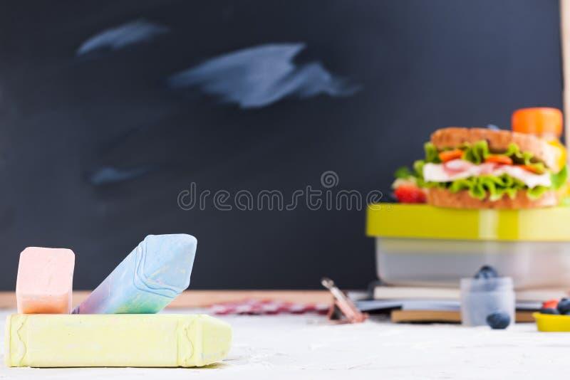 Κιβώτιο με το σχολικό μεσημεριανό γεύμα κοντά στο μαύρο πίνακα Υγιή τρόφιμα για ένα παιδί Φρυγανιά με τη σαλάτα και τις φράουλες  στοκ φωτογραφία