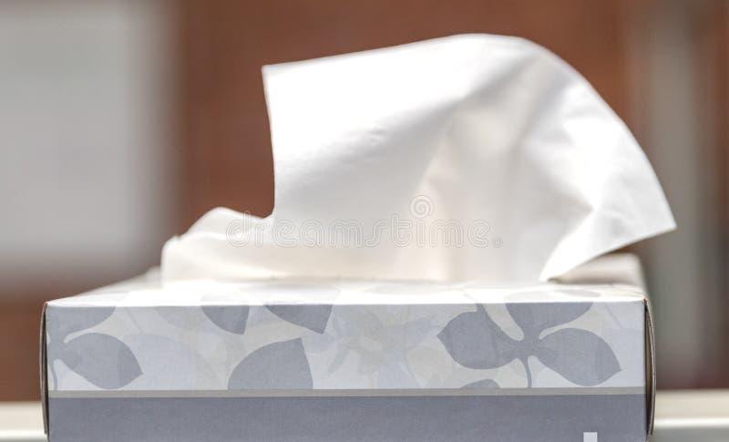 Κιβώτιο του ιστού χαρτομάντιλων καθαρισμού χωρίς το μαρκάρισμα στο κιβώτιο με το χέρι που τραβά το ένα έξω στοκ φωτογραφίες