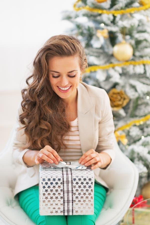 Κιβώτιο χριστουγεννιάτικου δώρου ανοίγματος γυναικών μπροστά από το χριστουγεννιάτικο δέντρο στοκ φωτογραφία με δικαίωμα ελεύθερης χρήσης